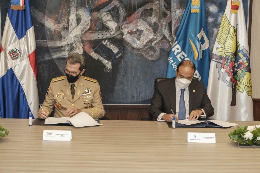 El administrador general de Banreservas, Samuel Pereyra, y el ministro de Defensa, teniente general Carlos Luciano Díaz Morfa, firman el acuerdo de cooperación que ofrecerá facilidades financieras a los miembros del cuerpo castrense.